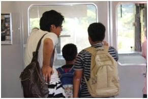 すたんどばいみーの小学生と帰りの電車を楽しむ高校生スタッフ